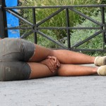 Homeless man in shorts sleeping with hands between knees