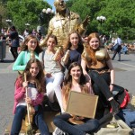 Man spray-painted gold poses with young girls
