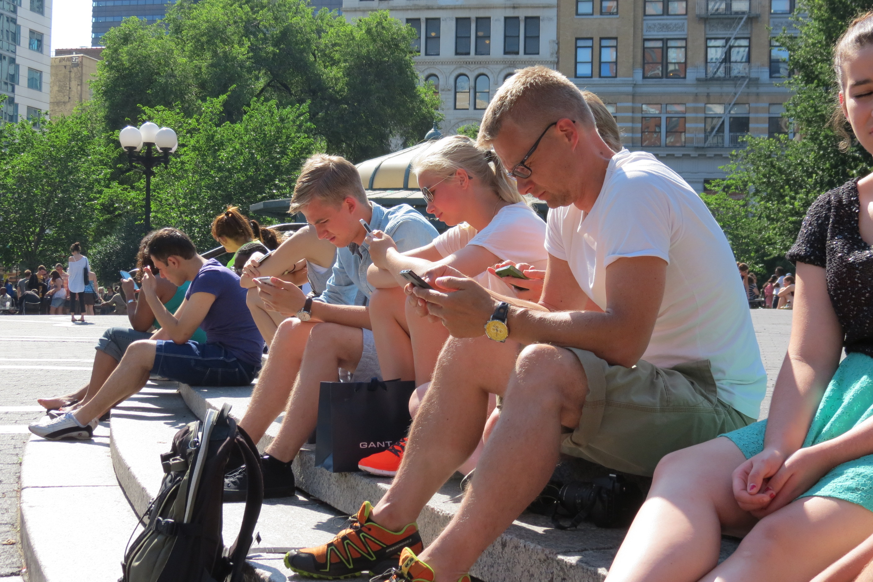 A tourist family in New York City ignore each other & stare at their phones