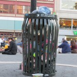 homeless man in a garbage can cage