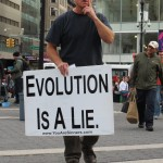 street preacher holding EVOLUTION IS A LIE sign