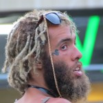 bearded man with flamboyant shades and snake tattoo near eye