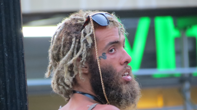 bearded man with flamboyant shades and snake tattoo near eye