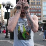 man with eyes tattooed on hands covering face