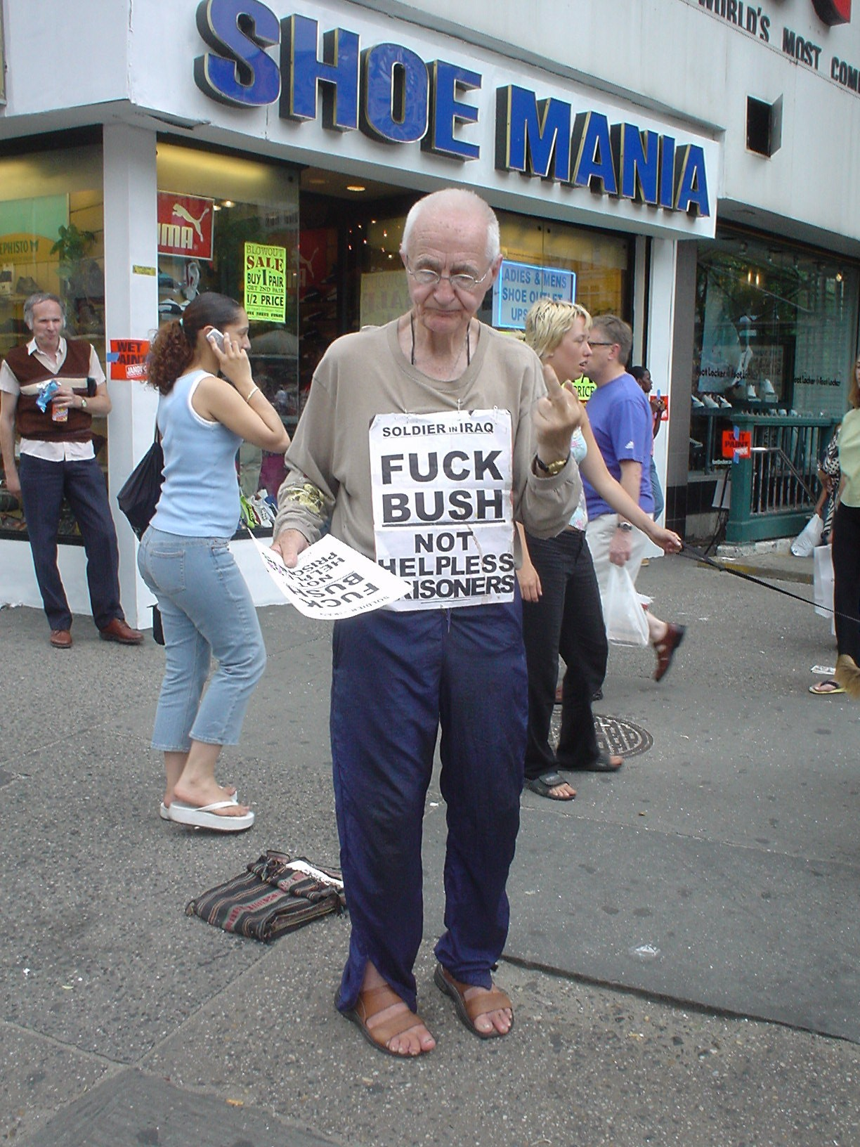 Old Man with FUCK BUSH sign gives the middle finger
