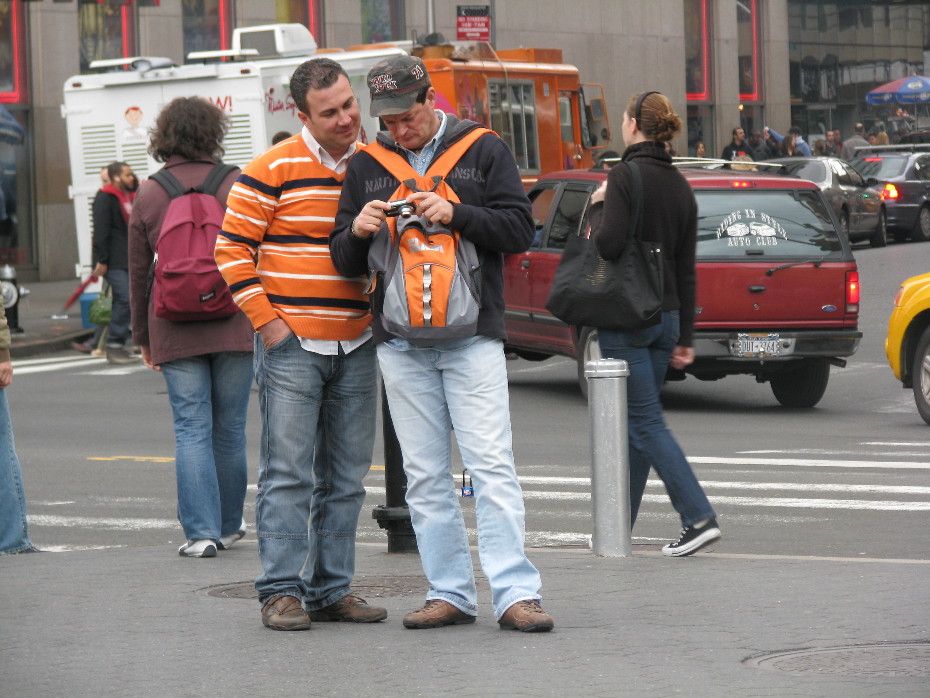 Tourists in orange wearing backpack in front so as not to get robbed
