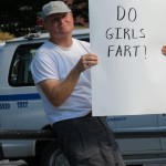 Roman with DO GIRLS FART? sign