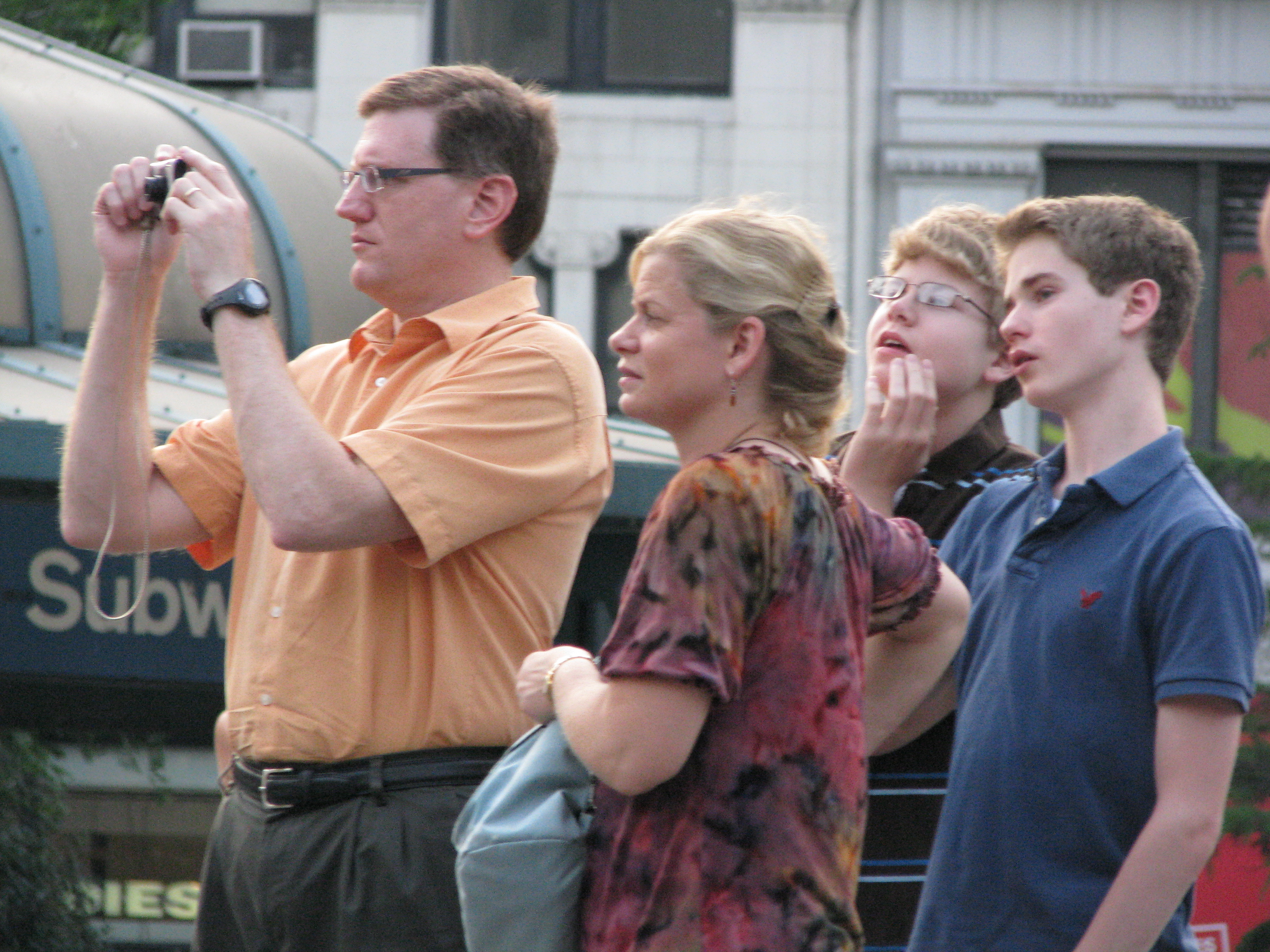 Father in a family of tourists taking a picture of NYC