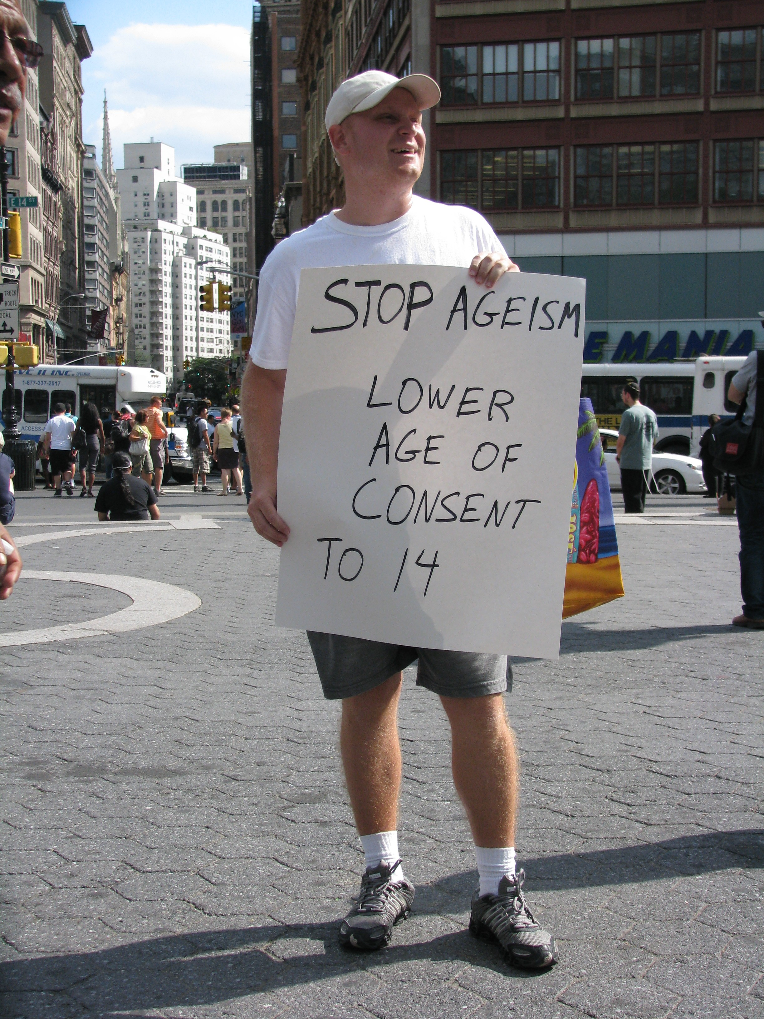 man with LOWER AGE OF CONSENT sign