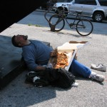 Man asleep under The Cube with pizza