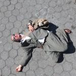 Lotion Man lying on floor of park