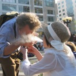 Woman blowing smoke in man's face while she lights his cigarette