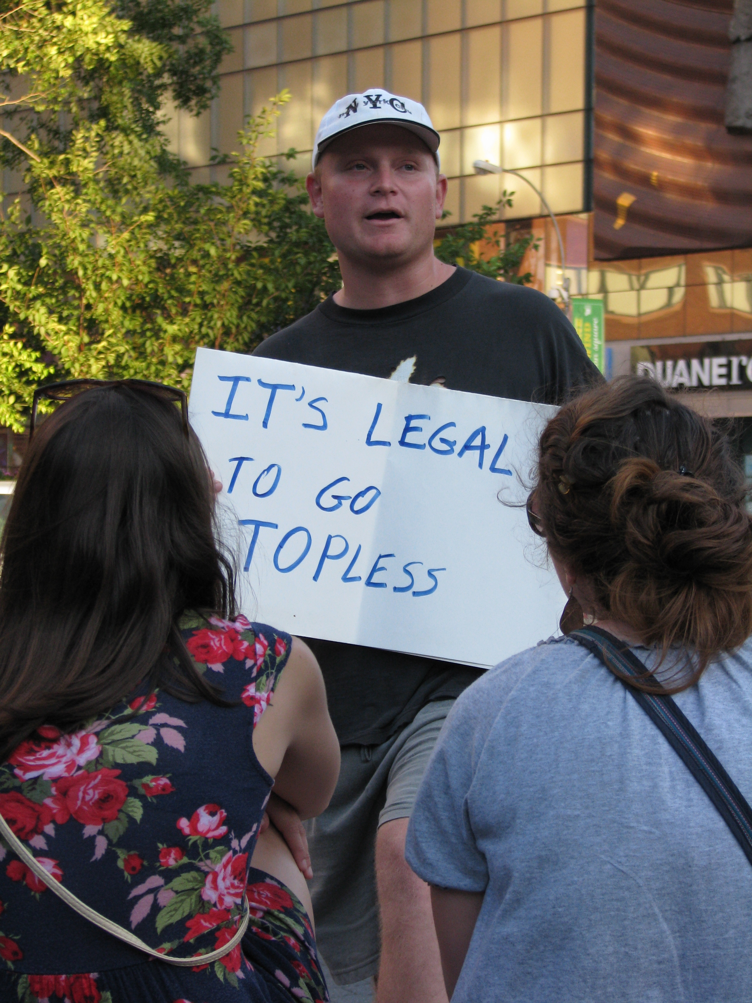 "man with ""IT'S LEGAL TO GO TOPLESS"" sign for the women of NYC"