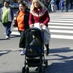 Man dressed as woman pushing cat in stroller
