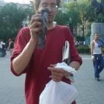 homeless man holding a sick pigeon