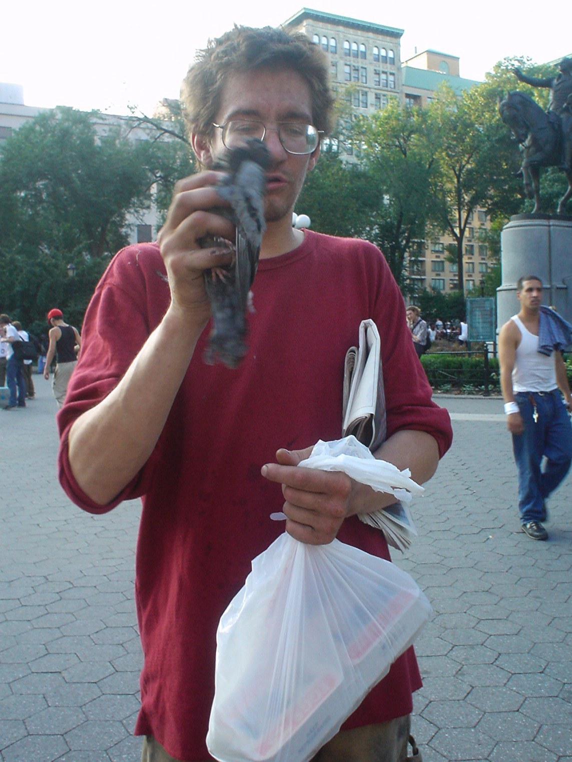 homeless man holding a sick pigeon
