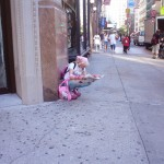 Pink girl reading paper up the street from Strand Books