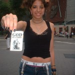 young girl with GOD IS FAKE flyer
