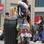 homeless fashion designer stands against garbage can